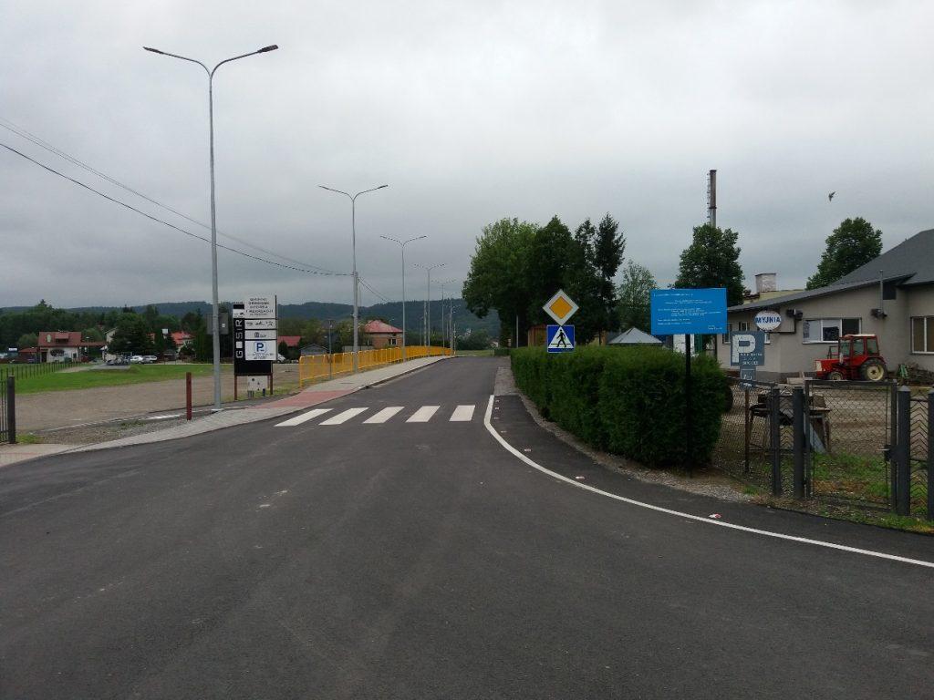 Fotografia przedstawia widok przebudowanej drogi gminnej nr 112156 R od strony skrzyżowania z drogą powiatową nr 1923 R. Na zdjęciu widoczna jest nowa nawierzchnia bitumiczna, chodnik wraz z barierkami i oświetleniem oraz oznakowane poziome przejście dla pieszych.
