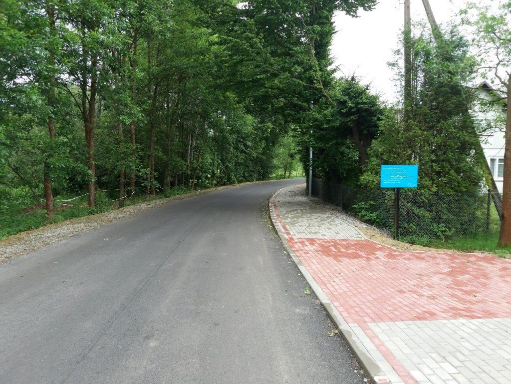Fotografia przedstawia widok przebudowanej drogi gminnej nr 112156 R od strony przejazdu kolejowego. Na zdjęciu widoczna jest nowo wykonana nawierzchnia bitumiczna oraz chodnik znajdujący się po prawej stronie jezdni.