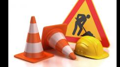 Na obrazku widnieje znak drogowy remont oraz pachołki drogowe jeden wywrócony i kask